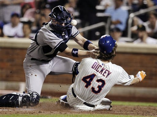New York Yankees catcher Chris Stewart cannot hold the ball as New York Mets' R.A. Dickey slides safely into home plate during the fifth inning of their baseball game at Citi Field in New York, Sunday, June 24, 2012. (AP Photo/Peter Morgan)