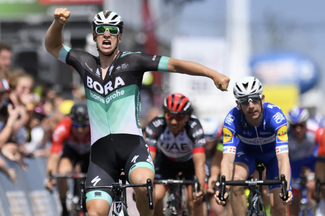 Pascal Ackermann from Germany of team Bora-Hansgrohe raises his arms after crossing the finish line to win the fifth and last stage, a 181,8 km race between Mont-sur-Rolle and Geneva during the 72th Tour de Romandie UCI ProTour cycling race in Geneva, Switzerland, Sunday, April 29, 2018. (Laurent Gillieron/Keystone via AP)