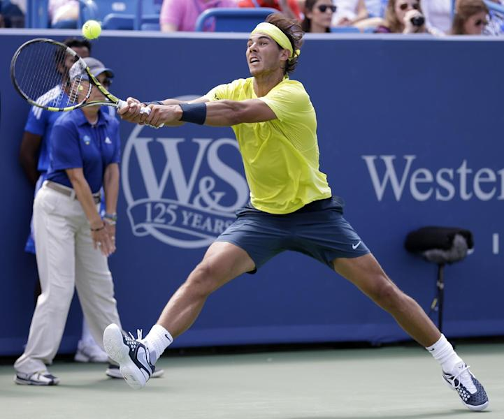 Rafael Nadal, from Spain, hits a backhand against John Isner during the finals match at the Western & Southern Open tennis tournament on Sunday, Aug. 18, 2013, in Mason, Ohio. Nadal won 7-6 (8), 7-6 (3). (AP Photo/Al Behrman)