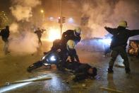 Colleagues try to help an injured police officer lying on the road after an attack by protesters during clashes in Athens, Tuesday, March 9, 2021. Severe clashes broke out Tuesday in Athens after youths protesting an incident of police violence attacked a police station with petrol bombs. (AP Photo/Aggelos Barai)