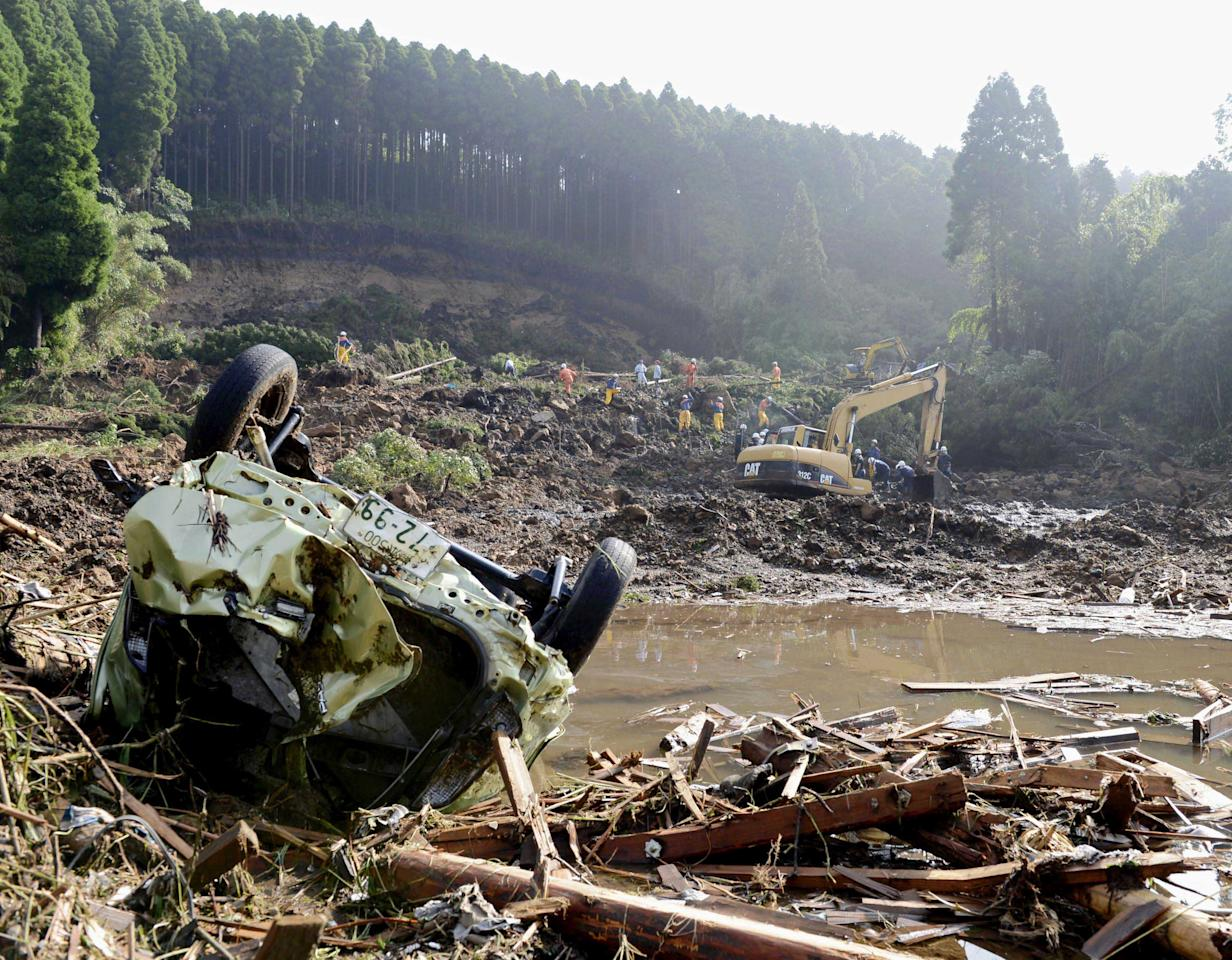 Rescue workers search for missing people at the scene of a landslide in Aso, Kumamoto Prefecture, Japan, Sunday, July 15, 2012. Heavy rain triggered flash floods and mudslides in southern Japan this week, killing about two dozens of people. (AP Photo/Kyodo News) JAPAN OUT, MANDATORY CREDIT, NO LICENSING IN JAPAN, CHINA, HONG KONG, SOUTH KOREA AND FRANCE