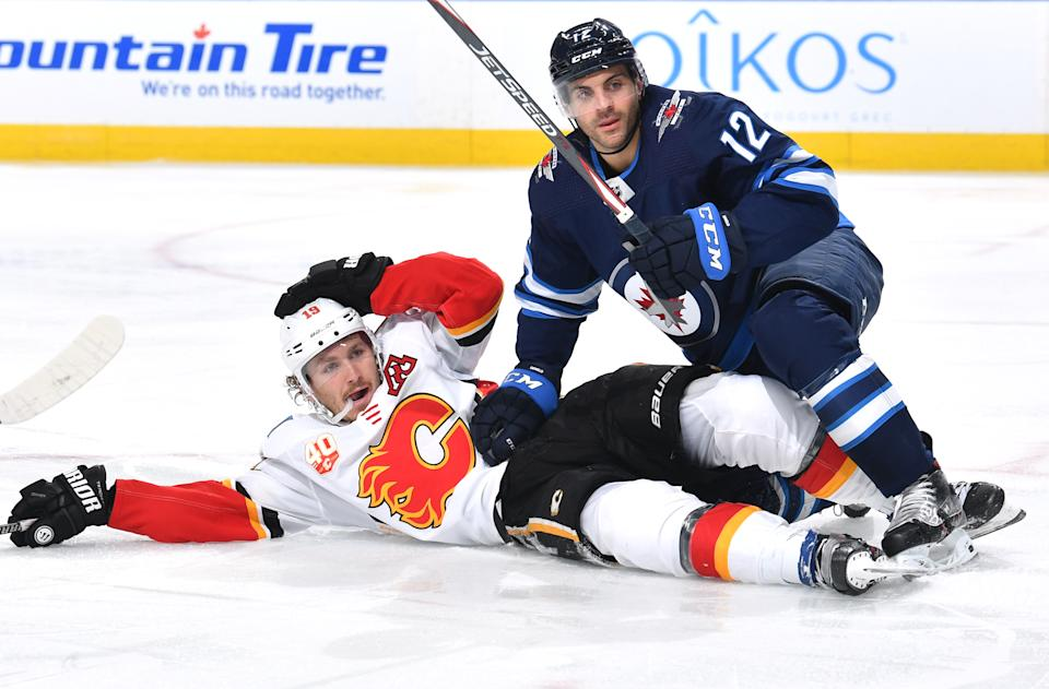 EDMONTON, ALBERTA - AUGUST 04: Dylan DeMelo #12 of the Winnipeg Jets puts keeps Matthew Tkachuk #19 of the Calgary Flames down during the third period of Game Three of the Western Conference Qualification Round at Rogers Place on August 04, 2020 in Edmonton, Alberta. (Photo by Andy Devlin/NHLI via Getty Images)
