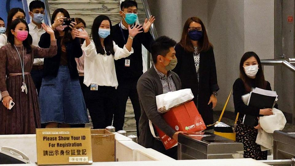 i-Cable TV news journalists leave with their boxes after being laid off in Hong Kong, China December 1, 2020