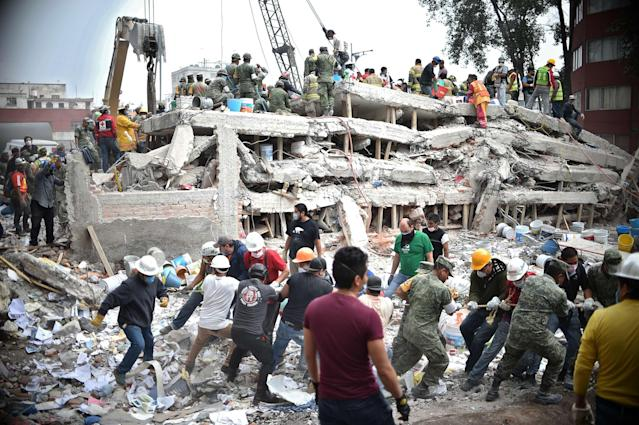 <p>Rescuers, firefighters, policemen, soldiers and volunteers search for survivors in a flattened building in Mexico City on Sept. 20, 2017 a day after a strong quake hit central Mexico. (Photo: Yuri Cortez/AFP/Getty Images) </p>