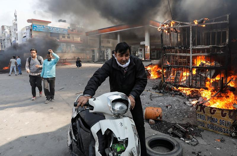 A man pushes his damaged scooter past a burning petrol pump during riots in Delhi.  (Photo: Danish Siddiqui / Reuters)