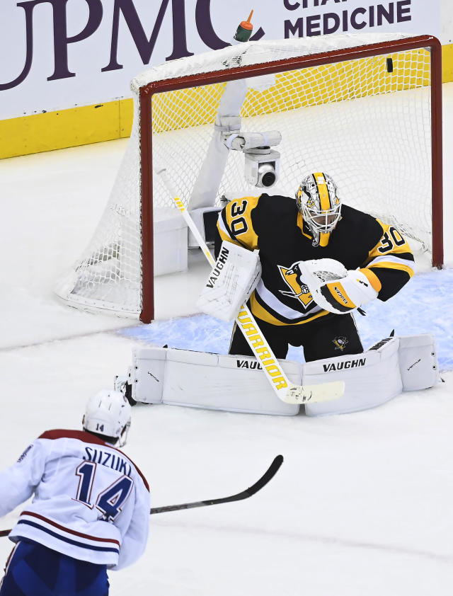 Montreal Canadiens center Nick Suzuki (14) scores past Pittsburgh Penguins goaltender Matt Murray (30) during the second period of an NHL hockey playoff game in Toronto, Saturday, Aug. 1, 2020. (Nathan Denette/The Canadian Press via AP)