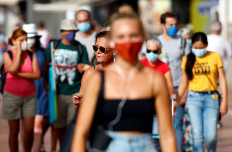 A woman smokes a cigarette while walking alongside other people wearing protective masks during the spread of the coronavirus disease (COVID-19) pandemic, in Las Palmas