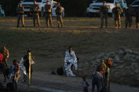 A migrant man and little boy stand wrapped in emergency blankets on the U.S. side of the Rio Grande river after they crossed the border to Del Rio, Texas, from Ciudad Acuna, Mexico, early Thursday, Sept. 23, 2021. (AP Photo/Fernando Llano)