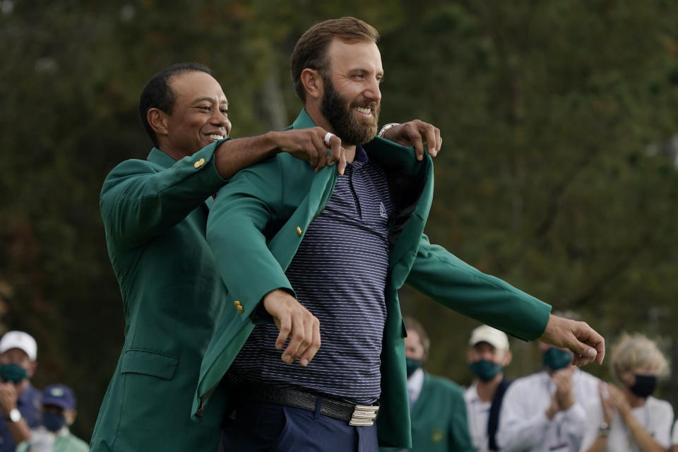 FILE - Tiger Woods helps Masters' champion Dustin Johnson with his green jacket after his victory at the Masters golf tournament in Augusta, Ga., in this Sunday, Nov. 15, 2020, file photo. It will be 144 days from when Tiger Woods helped Johnson into his green jacket until Johnson tees off in the opening round in his bid to join Woods, Nick Faldo and Jack Nicklaus as the only repeat winners at Augusta. (AP Photo/Charlie Riedel, File)