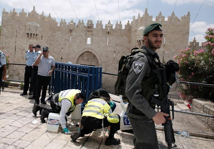Israeli Zaka emergency services clean the site of a stabbing attack carried out by an 18-year-old Palestinian on an Israeli border policeman on June 21, 2015, at the Damascus Gate outside the old city of Jerusalem (AFP Photo/Ahmad Gharabli)