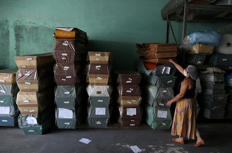 An employee at Viana Funeral services arranges coffins, during the COVID-19 coronavirus pandemic in Manaus, Brazil, where the City Hall has warned that stock of coffins in the region is likely to run out, on April 27, 2020. - Hospitals in Manaus have installed refrigerated containers to hold bodies that await funerals and mass grave sites have been dug to bury victims. (Photo by MICHAEL DANTAS / AFP) (Photo by MICHAEL DANTAS/AFP via Getty Images)