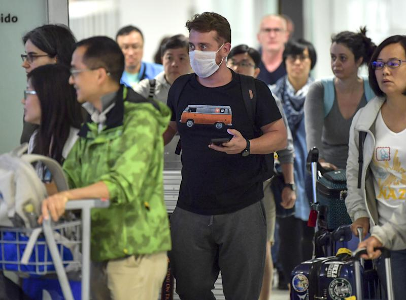 """A passengers, wearing a masks as a precautionary measure to avoid contracting the Covid-19 virus, travels through Guarulhos International Airport, in Guarulhos, Sao Paulo, Brazil on February 26, 2020. - The Brazilian Health Ministry confirmed Wednesday the diagnosis of coronavirus of a Brazilian resident in Sao Paulo, which became the first case of this epidemic in Latin America. The initial diagnosis """"was confirmed,"""" Minister Luiz Henrique Mandetta said at a press conference in Brasilia. (Photo by NELSON ALMEIDA / AFP) (Photo by NELSON ALMEIDA/AFP via Getty Images)"""