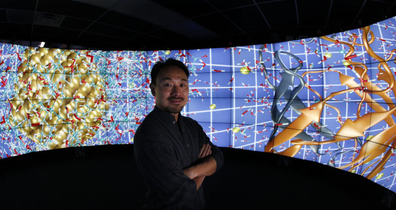 In this photo made Thursday, Jan. 24, 2013, in Chicago, University of Illinois-Chicago computer scientist Jason Leigh, co-inventor of the CAVE2 virtual reality system, stands in the CAVE2 where the system's 72 stereoscopic liquid crystal display panels encircles the viewer 320 degrees and creates a 3D environment that can take you to the bridge of the Starship Enterprise, a flyover the planet Mars, or through the blood vessels of the brain. (AP Photo/Charles Rex Arbogast)