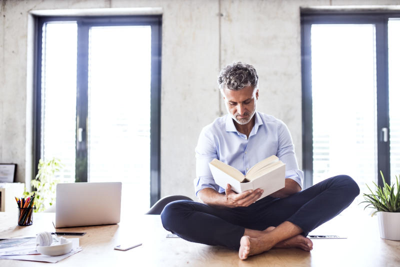 Mature businessman sitting barefoot on desk in office reading a book