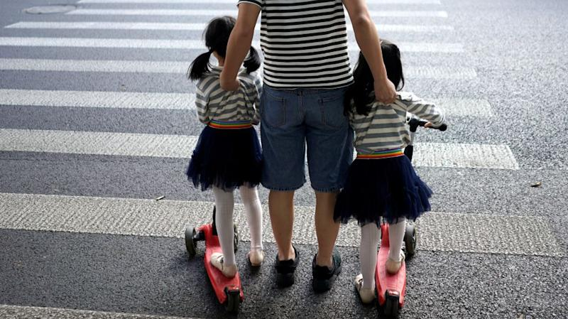 A father crosses a road with his twin daughters