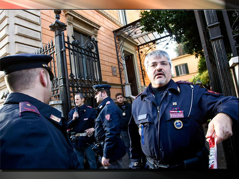 Police officers stand outside the Chilean embassy, Rome, Italy, on texture, partial graphic