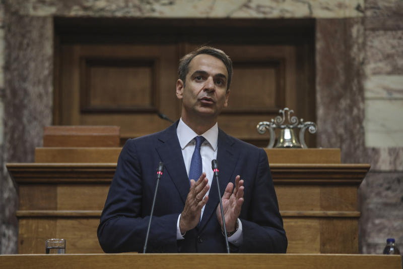 Greece's Prime Minister Kyriakos Mitsotakis, addresses lawmakers inside the parliament, in Athens, on Friday, July 19, 2019.  Prime Minister Kyriakos Mitsotakis' conservative New Democracy party returned to power after winning a general election earlier this month on a pledge to cut taxes imposed during Greece's three successive international bailouts. (AP Photo/Petros Giannakouris)