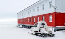 A military snowmobile is parked next to a building at the Russian northern military base on Kotelny island, beyond the Arctic circle