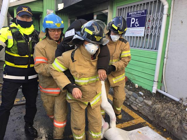 <p>A staff (C) of Miryang hospital is helped by firefighters in front of the damaged hospital after it was burned by a fire in Miryang, South Korea, Jan. 26, 2018. (Photo: Kim Hee-Chul EPA-EFE/REX/Shutterstock) </p>
