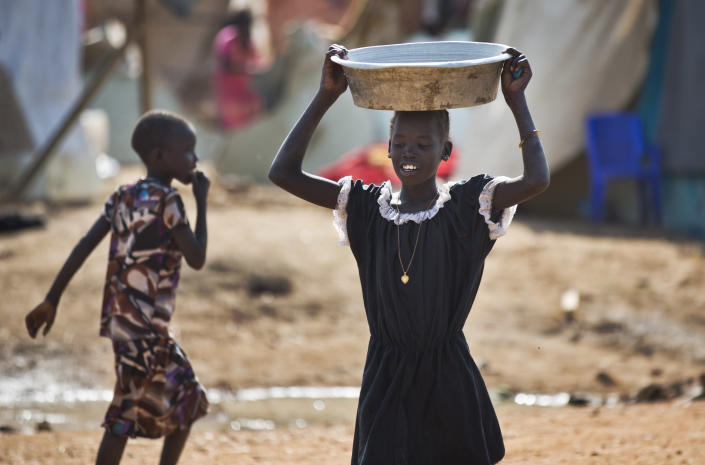 A displaced girl carries a bowl of water on her head at a United Nations compound which has become home to thousands of people displaced by the recent fighting, in the Jebel area on the outskirts of Juba, South Sudan, Tuesday, Dec. 31, 2013. Anti-government rebels took control of nearly all of the strategic city of Bor on Tuesday even as officials announced that representatives from the government and the rebels had agreed to hold talks for the first time. (AP Photo/Ben Curtis)