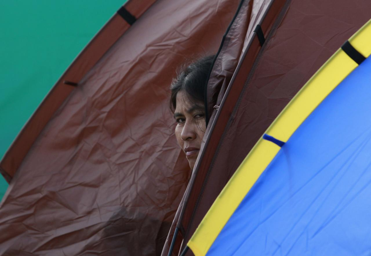 An anti-government protester looks out from her tent as she takes part in a rally at the Victory Monument in Bangkok January 21, 2014. Some Thai rice farmers have threatened to switch sides and join protesters trying to topple the government if they do not get paid for their crop, a worrying development for Prime Minister Yingluck Shinawatra whose support is based on the rural vote. REUTERS/Chaiwat Subprasom (THAILAND - Tags: POLITICS CIVIL UNREST TPX IMAGES OF THE DAY)