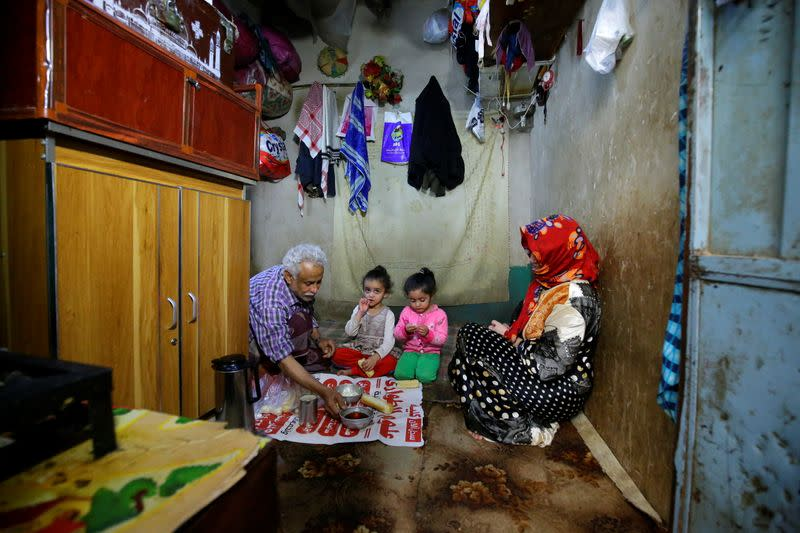 Ahmad Farea and his family sit for a meal at their house in Sanaa