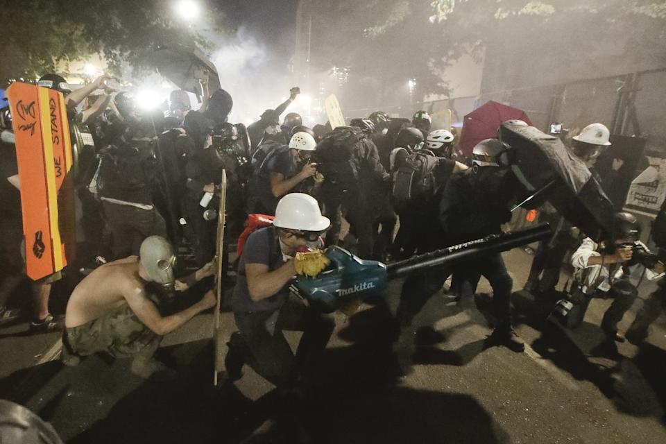 """Demonstrators huddle behinds makeshift shields and umbrellas as one uses a leaf blower to blow back tear gas fired by federal agents. <span class=""""copyright"""">(Marcio Jose Sanchez / Associated Press)</span>"""
