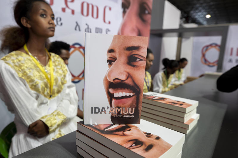 A customer purchase Prime Minister Dr Abiy Ahmed's book on MEDEMER (synergy) after it was launched Saturday Oct. 19, 2019, at the Ethiopian capital Addis Ababa. Ethiopia's Nobel Peace Prize-winning prime minister's book of his ideology, with one million copies already printed. Saturday's launch again raises concerns among some in the East African nation that a cult of personality could spring up around Prime Minister Abiy Ahmed, who announced sweeping political reforms after taking office last year.(AP Photo/Mulugeta Ayene)