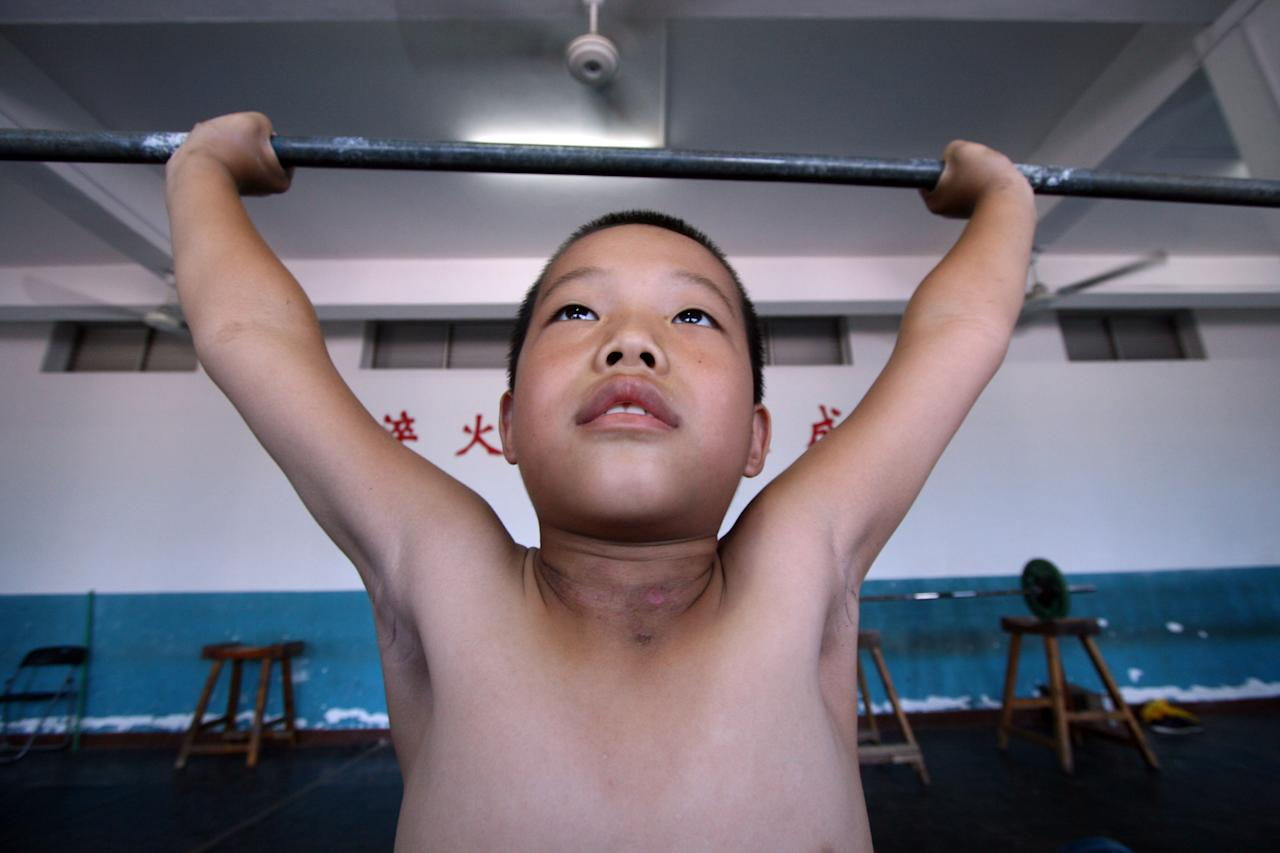 A Chinese boy practises weightlifting at a weightlifting training school in Jinjiang, in south China's Fujian province on July 22, 2011. Young Chinese athletes often enroll in sports schools in the hopes of future medal dreams following the country's success at the Beijing 2008 Olympic Games.     CHINA OUT AFP PHOTO (Photo credit should read STR/AFP/Getty Images)