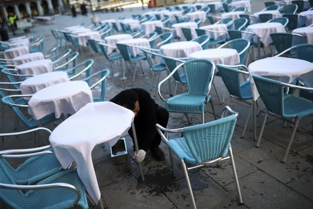 A waiter cleans tables and chairs in an empty restaurant terrace at St Mark's Square in Venice