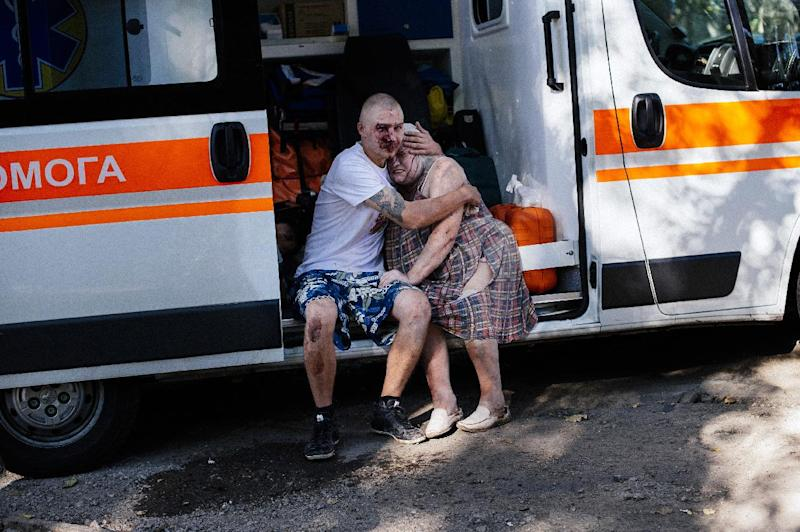 An injured man hugs a woman as they sit in an ambulance after shelling in the main separatist stronghold of Donetsk, eastern Ukraine, on August 23, 2014