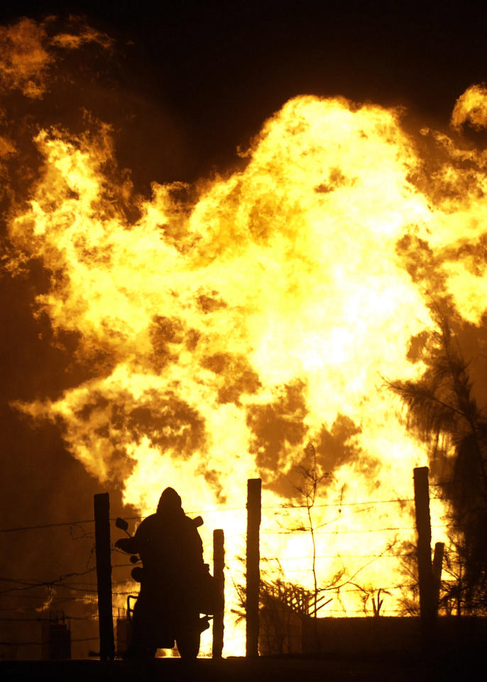 An Egyptian sitting astride his motorbike watches the leaping flames after masked gunmen blew up a terminal of the Egyptian natural gas pipeline to Israel and Jordan in El Arish,in the northern part of Egypt's Sinai Peninsula, early, Tuesday, July 12 2011, Security officials say. (AP Photo)