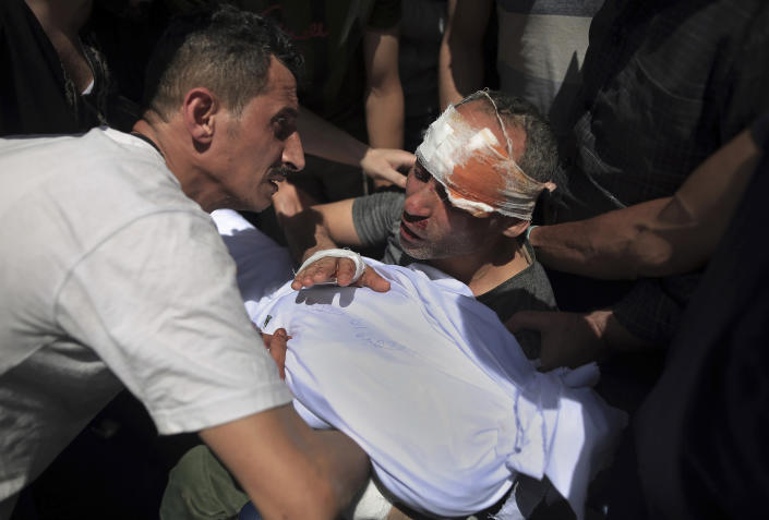 A injured Palestinian man mourns over the body of his young son, who was killed in overnight Israeli airstrikes, in Gaza City, Sunday, May 16, 2021. (AP Photo/Sanad Latifa)