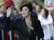 FILE - In this Aug. 1, 2017 file photo, Thailand's former Prime Minister Yingluck Shinawatra waves to supporters as she arrives at the Supreme Court in Bangkok, Thailand. Afghan President Ashraf Ghani, driven out by the Taliban, is the latest leader on the run to turn up in the United Arab Emirates. Others who found refuge in the Gulf Arab state include Shinawatr, former Pakistani prime minister Benazir Bhutto, Palestinian Mohammed Dahlan, and Spain's King Juan Carlos who is facing financial probe. (AP Photo/Sakchai Lalit, File)