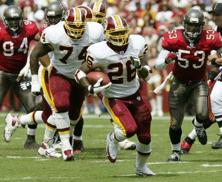Washington Redskins Clinton Portis (26) breaks away to score a touchdown followed by teammate Kenyatta Jones (74), Tampa Bay Buccaneers' Ton Warner (94), and Shelton Quarles (53) during the first quarter of the NFL season opener at FedEx Field in Landover, Maryland September 12, 2004. REUTERS/Molly Riley