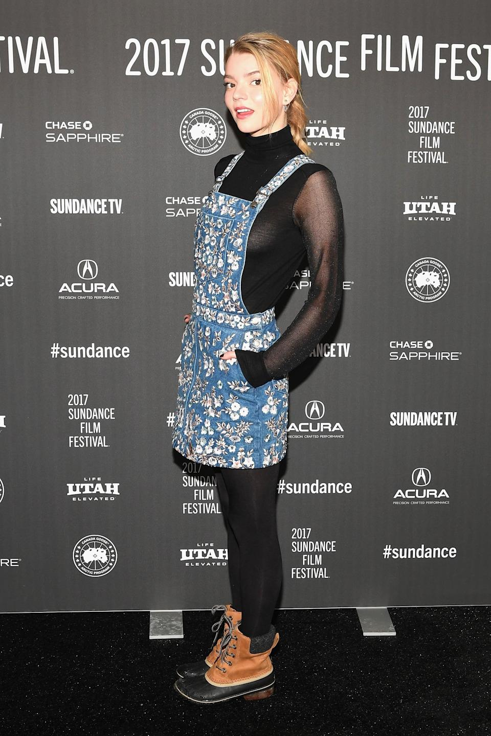 <p>Anya kept off the chill of Sundance in her embellished denim pinafore dress.</p>
