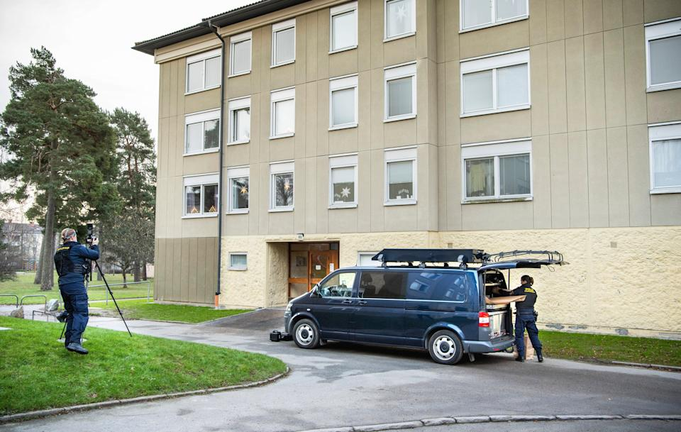 <p>Police at the apartment block in Stockholm where a woman allegedly locked up her son for three decades</p> (AP)