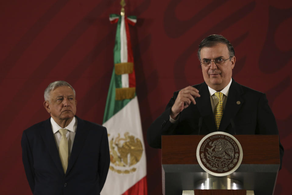 Mexican President Andres Manuel Lopez Obrador listens to Marcelo Ebrard, his Secretary of Foreign Affairs, during a daily morning press conference at the National Palace in Mexico City, Friday, Nov. 29, 2019.(AP Photo/Marco Ugarte)