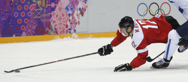 Austria forward Michael Raffl dives for control of the puck against Finland in the first period of a men's ice hockey game at the 2014 Winter Olympics, Thursday, Feb. 13, 2014, in Sochi, Russia. (AP Photo/Julio Cortez)