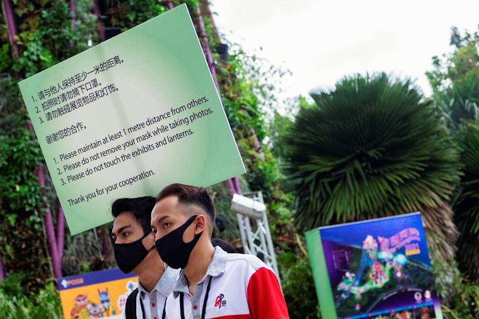 Event marshals carry a sign to remind visitors to comply with measures to curb the coronavirus disease (COVID-19) outbreak during the annual River Hongbao festival on the eve of the Chinese Lunar New Year of the Ox, otherwise known as the Spring Festival, at Singapore's Gardens by the Bay, February 11, 2021. REUTERS/Loriene Perera