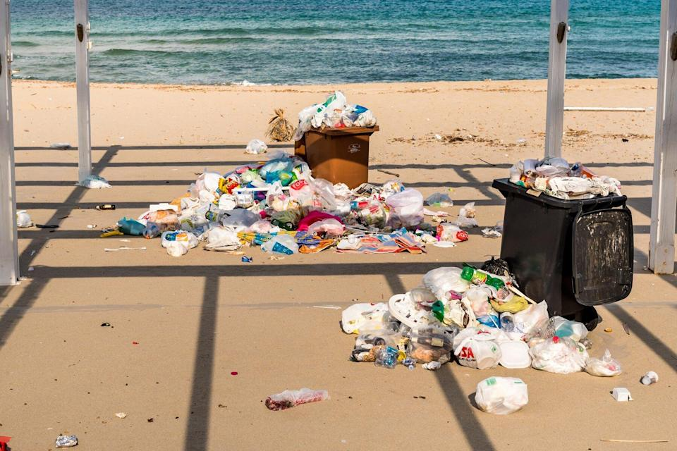 Containers with garbage on the sand at the Isola delle Femmine in Sicily.