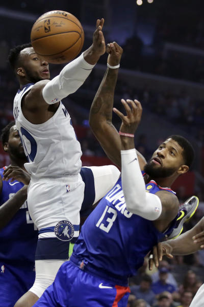 Minnesota Timberwolves guard Josh Okogie, left, battles Los Angeles Clippers guard Paul George, right, for a loose ball during the first half of an NBA basketball game in Los Angeles, Saturday, Feb. 1, 2020. (AP Photo/Alex Gallardo)