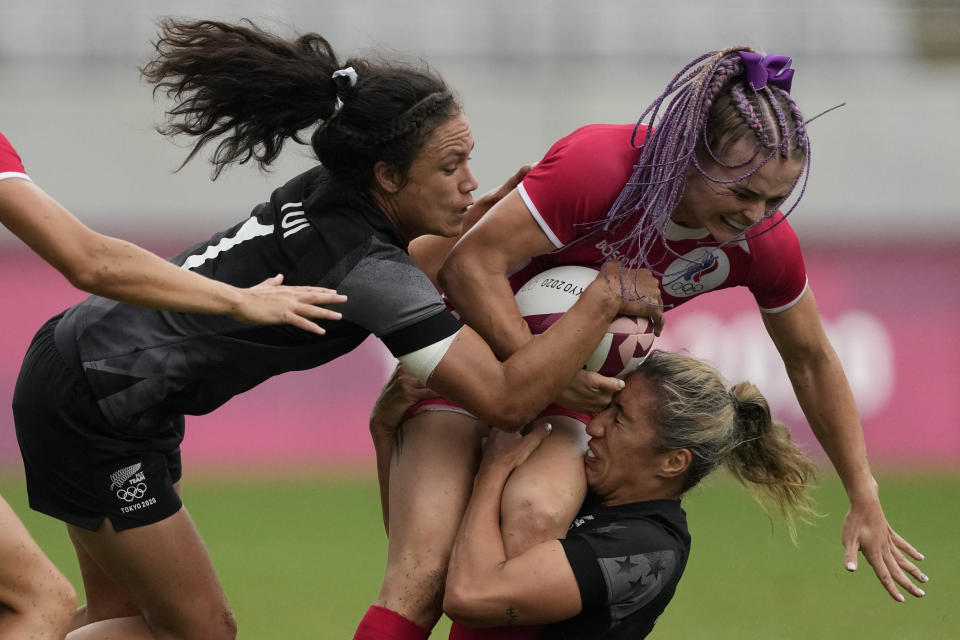 Russian Olympic Committee's Alena Tiron, right, is taken down by New Zealand's Sarah Hirini, bottom, and Ruby Tui, in their women's rugby sevens match at the 2020 Summer Olympics, Friday, July 30, 2021 in Tokyo, Japan. (AP Photo/Shuji Kajiyama)