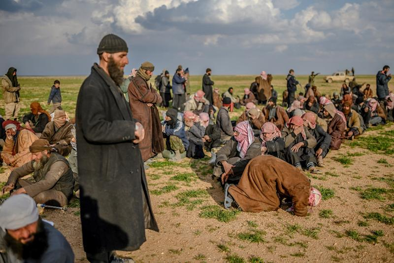Suspected Islamic State group fighters pray as they wait to be searched and interrogated after leaving the jihadists' last holdout in eastern Syria (AFP Photo/Bulent KILIC)