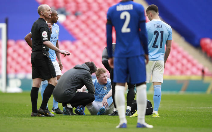 Manchester City's Kevin De Bruyne sits on the field after injuring during the English FA Cup semifinal soccer match between Chelsea and Manchester City at Wembley Stadium in London, England, Saturday, April 17, 2021. (AP Photo/Ian Walton, Pool)