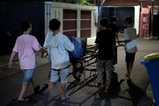 The motley group of children yell and bang on tambourines and drums as they roam the quiet streets of Indonesia's capital