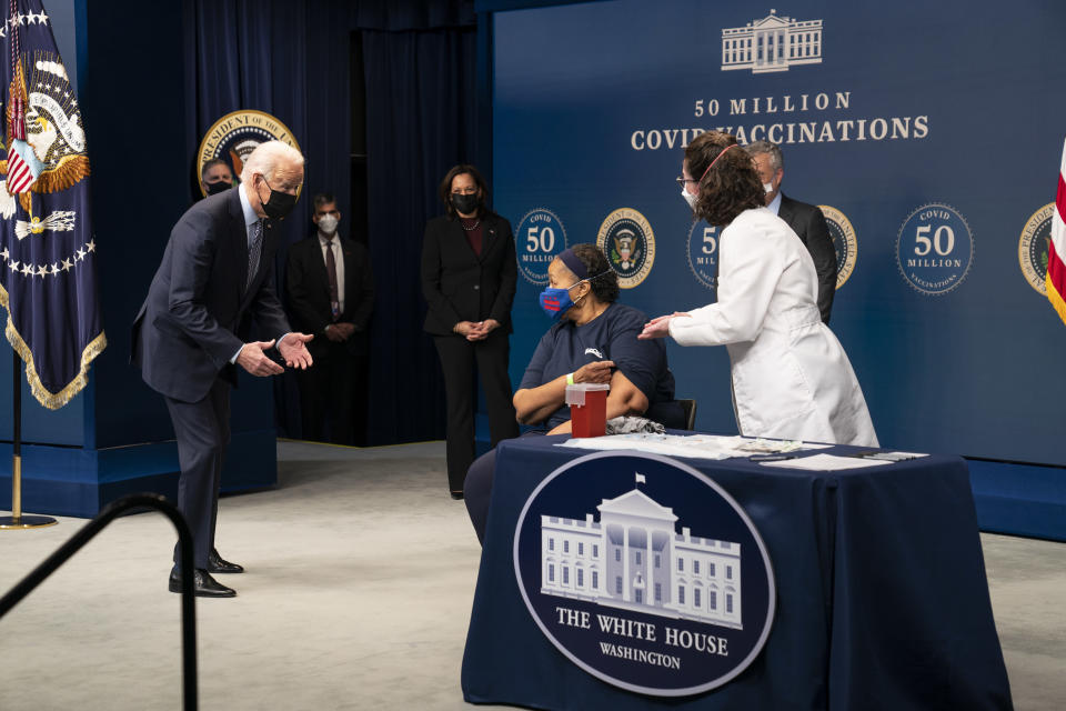President Joe Biden talks to Linda Bussey before she received a vaccination, during an event to commemorate the 50 millionth COVID-19 shot, in the South Court Auditorium on the White House campus, Thursday, Feb. 25, 2021, in Washington. (AP Photo/Evan Vucci)