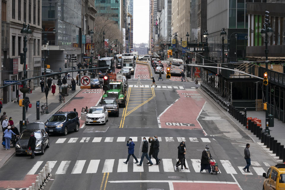 Pedestrians cross 42nd Street, Thursday, March 4, 2021, in New York. A year after the pandemic began, the nation's largest metropolis is adapting and showing new life. (AP Photo/Mark Lennihan)