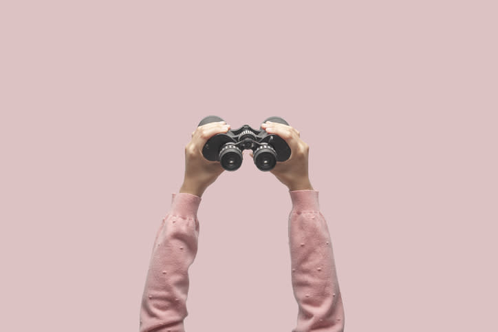 A pair of hands holding a pair of binoculars overhead.