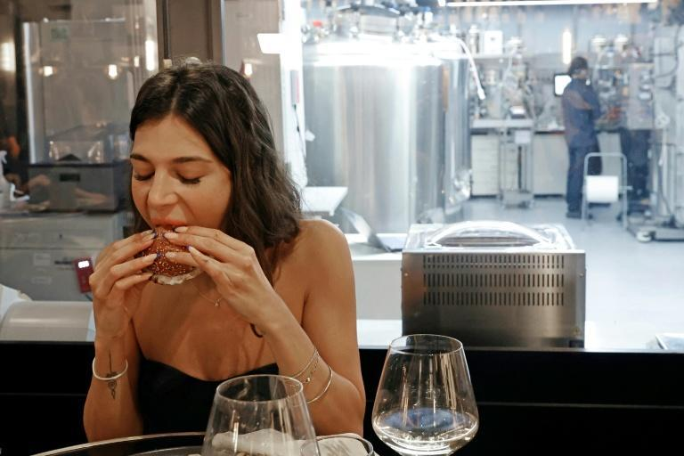 A diner eats a burger made with 'cultured chicken' meat at a restaurant adjoining the SuperMeat production site in the central Israeli town of Ness Ziona